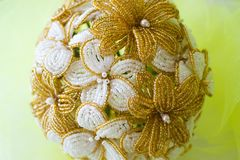 Wedding bouquet golden and white flowers from beads. On a yellow blurred background. royalty free stock photography