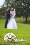 Wedding bouquet on the grass. Against groom and bride Royalty Free Stock Photography
