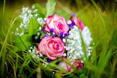 Wedding bouquet on the grass. Wedding bouquet of pink roses lies on autumn grass Stock Image