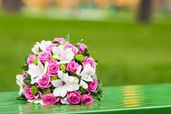 Wedding bouquet on a green bench. Bridal bouquet le lies on a bench on a green background on a summer day Stock Photography