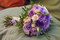 Wedding bouquet on a green cushion, bouquet of bride from rose c. Ream spray, rose bush, rose purple Memory Lane, violet eustoma, eucalyptus royalty free stock images