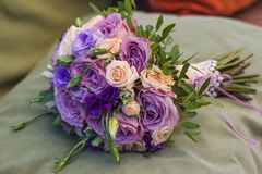 Wedding bouquet on a green cushion, bouquet of bride from rose c. Ream spray, rose bush, rose purple Memory Lane, violet eustoma, eucalyptus stock photo