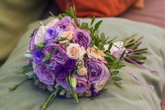 Wedding bouquet on a green cushion, bouquet of bride from rose cream spray, rose bush, rose purple Memory Lane, violet eustoma, eu. Calyptus royalty free stock photo