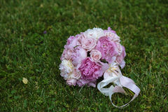 Wedding bouquet on green grass. Bride's flowers Stock Image