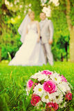 Wedding bouquet on green grass and verry blurred young wedding c Royalty Free Stock Image