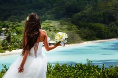 Wedding bouquet and groom. Wedding bouquet of frangipani and groom against the background the bay Seychelles Royalty Free Stock Photo