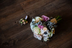 Wedding bouquet with grooms boutonniere of white and red roses on dark wooden background Royalty Free Stock Photo