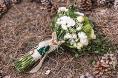Wedding bouquet. On the ground on spruce litter around cones Royalty Free Stock Photos