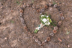 Wedding bouquet. On the ground on spruce litter around cones Stock Image
