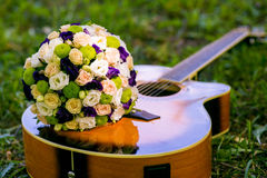 Wedding bouquet and guitar Stock Images