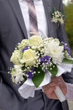 Wedding bouquet in a hand of the bride. Against a suit of the groom Royalty Free Stock Image