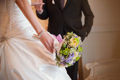 Wedding bouquet in in the hand of bride with groom Stock Photos