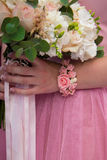 Wedding bouquet in hand. The bride is holding a wedding bouquet of roses in her hand Royalty Free Stock Photos