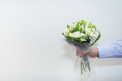 Wedding bouquet in a hand of the groom. On white background Royalty Free Stock Image