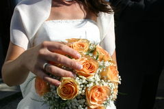 Wedding bouquet in the hands of the bride. Orange and white wedding bouquet in the hands of the bride. She's wearing the ring already Stock Photography