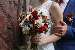 Wedding bouquet in hands of bride against the background of vint Royalty Free Stock Photo