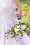 Wedding bouquet. In hands of the bride on background of the dress Stock Photography