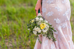 Wedding bouquet. In hands of the bride on background of the dress Stock Photos
