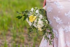 Wedding bouquet. In hands of the bride on background of the dress Stock Photo