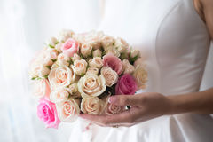 Wedding bouquet in hands of bride. Beautiful wedding bouquet of delicate beige roses in hands of bride Royalty Free Stock Image