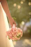 Wedding bouquet in hands of the bride. Beautiful bouquet of different colors in the hand of the bride in a white dress royalty free stock images
