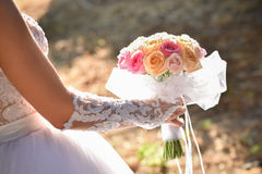 Wedding bouquet in hands of the bride. Beautiful bouquet of different colors in the hands of the bride in a white dress stock image