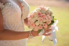 Wedding bouquet in hands of the bride. Beautiful bouquet of different colors in the hands of the bride in a white dress royalty free stock photo
