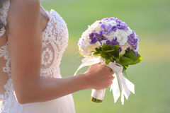 Wedding bouquet in hands of the bride. Beautiful bouquet of different colors in the hands of the bride in a white dress royalty free stock photography