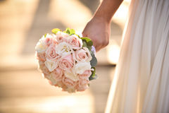Wedding bouquet in hands of the bride. Beautiful bouquet of different colors in the hands of the bride in a white dress stock photography