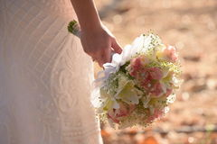 Wedding bouquet in hands of the bride. Beautiful bouquet of different colors in the hands of the bride in a white dress stock photos