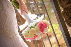 Wedding bouquet in hands of the bride. Beautiful bouquet of different colors in the hands of the bride in a white dress royalty free stock images