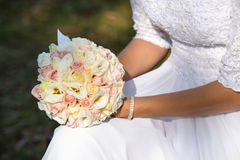 Wedding bouquet in hands of the bride. Beautiful bouquet of different colors in the hands of the bride in a white dress stock photo