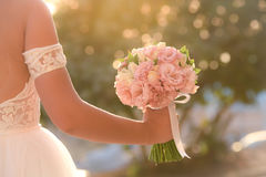 Wedding bouquet in hands of the bride. Beautiful bouquet of different colors in the hands of the bride in a white dress stock images