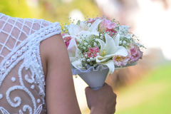 Wedding bouquet in hands of the bride. Beautiful bouquet of different colors in the hands of the bride in a white dress royalty free stock image
