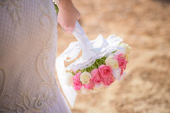 Wedding bouquet in hands of the bride. Beautiful bouquet of roses in the hands of the bride in a white dress royalty free stock photos