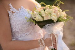 Wedding bouquet in hands of the bride. Beautiful bouquet of roses in the hands of the bride in a white dress royalty free stock photography