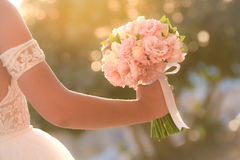 Wedding bouquet in hands of the bride. Beautiful bouquet in the hands of the bride in a white dress royalty free stock images