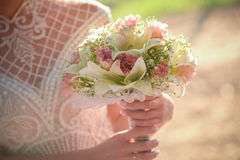 Wedding bouquet in hands of the bride. Elegant bouquet of different colors in the hands of the bride in a white dress royalty free stock images
