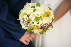 Wedding bouquet in hands of the bride and groom Royalty Free Stock Images