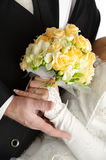 Wedding bouquet in hands of bride and groom, on wh. Rose flowers wedding bouquet, hands of bride and groom, traditional black and white wedding dress, on white Stock Photography