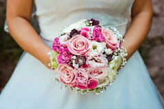 Wedding bouquet in the hands of the bride stock images