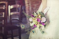 Wedding bouquet in hands of the bride. Old styled photo. Royalty Free Stock Image