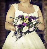 Wedding bouquet in hands of the bride. Old styled photo. Royalty Free Stock Photos