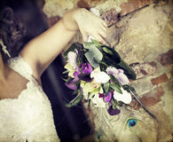Wedding bouquet in hands of the bride. Old styled photo. Royalty Free Stock Photo