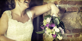 Wedding bouquet in hands of the bride. Old styled photo. Stock Photography