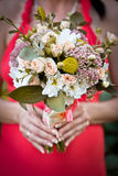 Wedding bouquet in hands of bride. Bride in a red dress Stock Photo