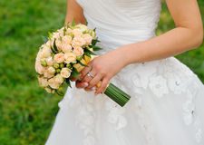 Wedding bouquet in hands of the bride with roses cream Stock Photography