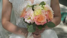 Wedding bouquet in the hands of the bride. Sunny day, colorful roses, close-up. stock video footage