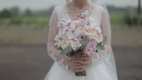 Wedding bouquet in the hands of the bride. Wedding day. Engagement. Pretty and well-groomed woman. Slow motion stock video