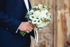 Wedding bouquet in the hands. Of groom Stock Photography